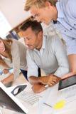Команда дизайнеров проверяя информацию на компьютере Стоковые Изображения