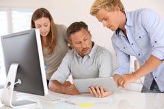 Команда дизайнеров проверяя новости на таблетке Стоковое Изображение