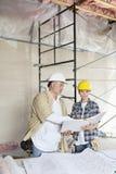 Команда конструкции смотря бумагу с светокопиями на таблице Стоковое Фото