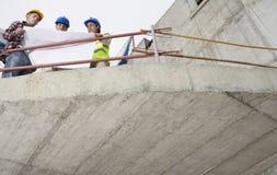 Команда конструкции с планами здания на месте Стоковые Фото