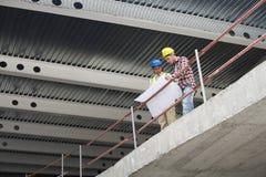 Команда конструкции с планами здания на месте Стоковое Изображение