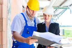 Команда конструкции с планами здания на месте Стоковое фото RF
