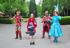 Команда костюмированных характеров стороны приветствуя гостя в парке атракционов Efteling Стоковое фото RF