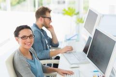 Команда молодых дизайнеров работая на столе при женщина усмехаясь на камере Стоковая Фотография RF