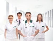 Команда молодых кавказских докторов в белых одеждах стоковое фото rf