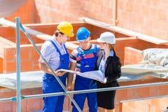 Команда обсуждая планы конструкции или строительной площадки Стоковые Изображения