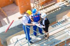 Команда обсуждая планы конструкции или строительной площадки Стоковое фото RF