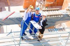 Команда обсуждая планы конструкции или строительной площадки Стоковая Фотография RF