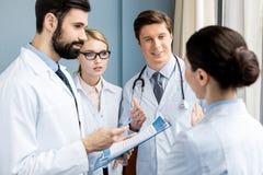 Команда докторов обсуждая диагноз Стоковые Изображения