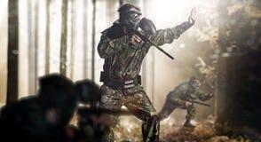 Команда пейнтбола в положении леса действия стоковая фотография