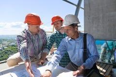 Команда построителей работая с светокопией на архитекторе места объясняет план строительства объединяться в команду инженеры Og Стоковые Изображения