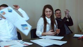 Команда профессионалов, сидя вокруг хода стола переговоров их бумаги видеоматериал