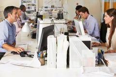 Команда работая на столах в занятом офисе Стоковые Изображения