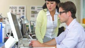 Команда работая на столах в многодельном офисе сток-видео