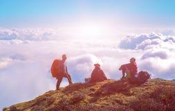 Команда силуэтов Hikers горы над облаками и светя Солнцем Стоковые Изображения RF