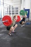 Команда тренирует сидения на корточках в центре спортзала фитнеса Стоковые Фотографии RF