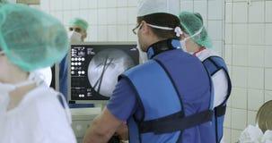 Команда хирургов контролирует деятельность на дисплеях видеоматериал