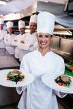 Команда шеф-поваров с представляя блюдами одним Стоковое Изображение RF