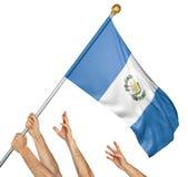 Команда людей вручает поднимать национальный флаг Гватемалы Стоковые Изображения