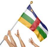Команда людей вручает поднимать национальный флаг Центральноафриканской Республики, перевод 3D изолированный на белой предпосылке Стоковое Изображение