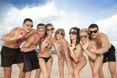 Команда друзей имея потеху на пляже Стоковая Фотография