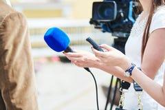 Комментарий новостей репортер при микрофон делая интервью стоковые фотографии rf