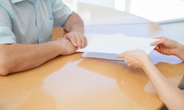 Коммерсантка давая к документам бизнесмена для подписки Стоковые Изображения