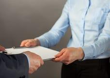 Коммерсантка давая к документам бизнесмена Стоковая Фотография RF