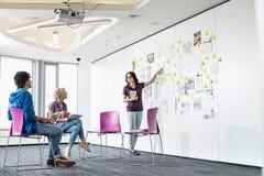 Коммерсантка давая представление к коллегам в творческих размерах офиса Стоковая Фотография RF