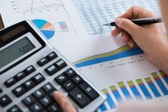 Коммерсантка анализируя финансовый отчет с калькулятором Стоковое Изображение