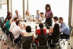 Коммерсантка адресуя встречу вокруг таблицы зала заседаний правления стоковое изображение