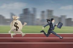 Коммерсантка бежать с сумкой доллара стоковое изображение