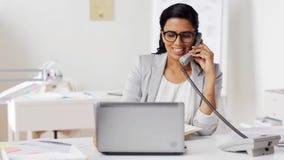 Коммерсантка вызывая на телефоне на офисе акции видеоматериалы
