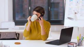 Коммерсантка вызывая на smartphone на офисе акции видеоматериалы