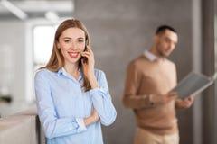 Коммерсантка вызывая на smartphone на офисе Стоковые Изображения
