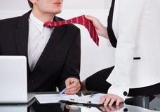 Коммерсантка вытягивая связь мужского коллеги пока сокращающ его Стоковое фото RF