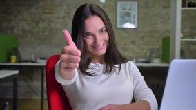 Коммерсантка в офисе наблюдает к камере и кладет ее палец до шоу подобие и уважение сток-видео