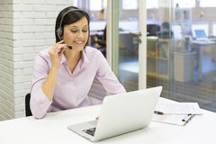 Коммерсантка в офисе на телефоне с шлемофоном, Skype Стоковые Изображения RF
