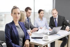 Коммерсантка в офисе с командой на задней части стоковая фотография rf