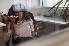 Коммерсантка говоря над мобильным телефоном на громкоговорителе пока wor Стоковая Фотография