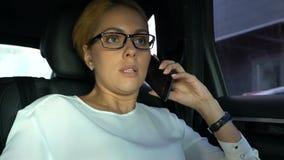 Коммерсантка говоря на мобильном телефоне с менеджером, давая устройство рабочих инструкций видеоматериал