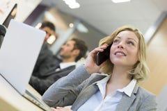 Коммерсантка говоря на мобильном телефоне в современном офисе Стоковая Фотография
