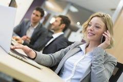 Коммерсантка говоря на мобильном телефоне в современном офисе Стоковые Фотографии RF