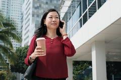 Коммерсантка говоря на сотовом телефоне и коммутируя стоковое фото rf
