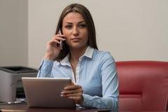 Коммерсантка говоря на телефоне в офисе Стоковые Фотографии RF