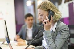 Коммерсантка говоря на телефоне в современном офисе Стоковое Изображение RF