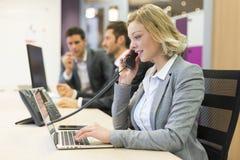 Коммерсантка говоря на телефоне в современном офисе Стоковые Фотографии RF