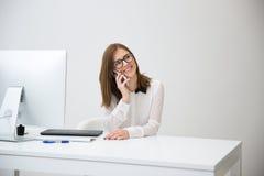 Коммерсантка говоря на телефоне на ее рабочем месте Стоковая Фотография