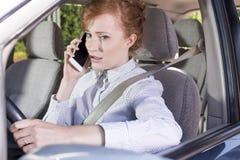 Коммерсантка говоря на телефоне пока управляющ автомобилем Стоковые Изображения