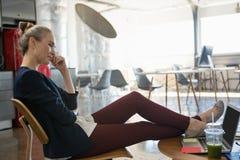 Коммерсантка говоря на умном телефоне пока ослабляющ на стуле на офисе Стоковое Изображение